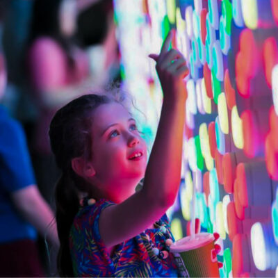 Young girl interacts with colourful interactive artwork A Light Touch by digital agency S1T2.