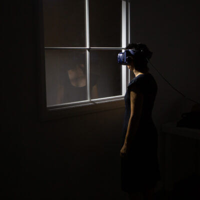 Woman in virtual reality headset experiences Edge of the Present mixed reality experience.
