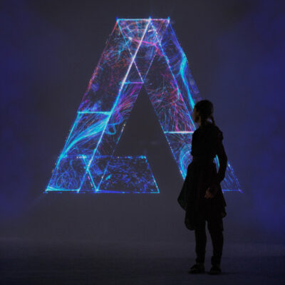 Woman stands in front of the final S1T2 Adobe Remix logo.