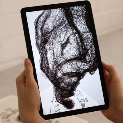 Person holds tablet with augmented reality coffee particle visualisation for Nespresso AR by creative agency S1T2.