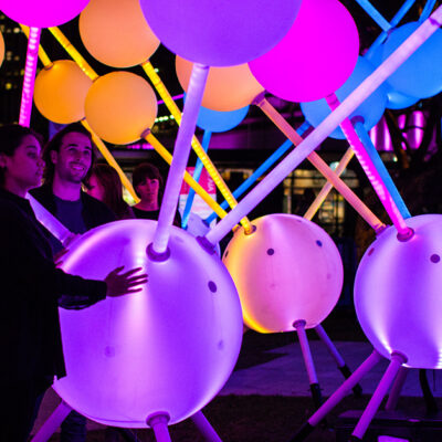 Two visitors interact with light installation Alzheimer's Affinity at Sydney's Vivid Festival.