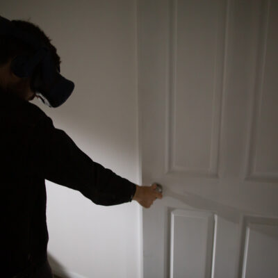 Man in virtual reality headset interacts with a door as part of Edge of the Present mixed reality experience.