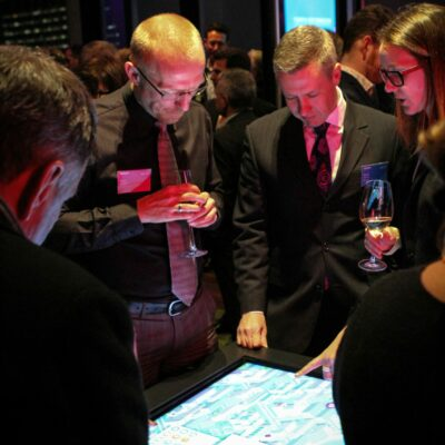 Group of Vivid Ideas event attendees in Sydney interact with a multi-touch table as part of AECOM Reconnected City digital marketing installation.