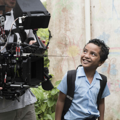 Fijian boy looks up at cinematographer carrying video camera gear during filming for UNICEF Draw the Line.