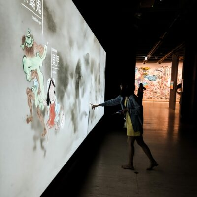 Woman use her hand to trigger an interaction point for projection animations at Japan Supernatural.