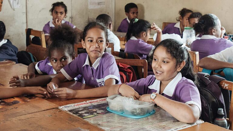 Children in Fiji eat lunch in a classroom.