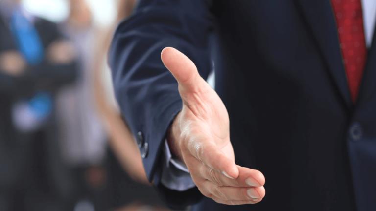 Corporate man holding hand for handshake.