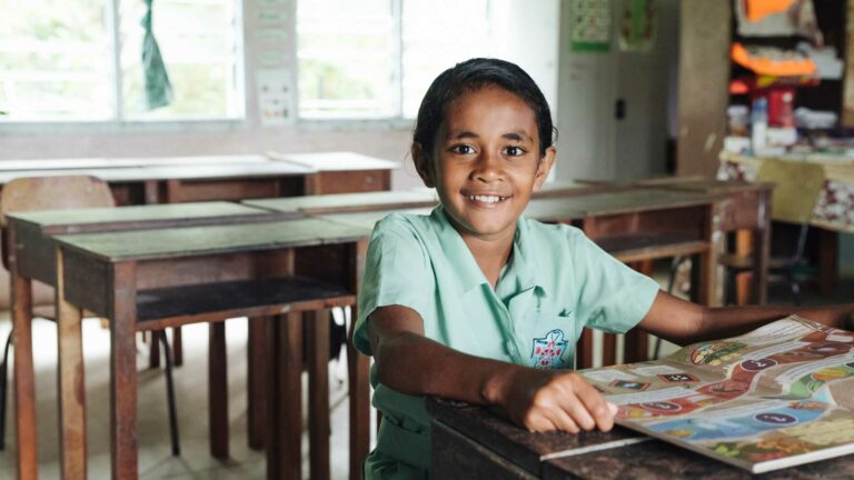 A Fijian student looks through a Beyond the Stars storybook in her classroom.