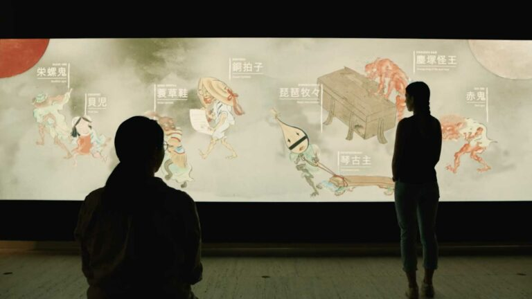 Woman looks at animated yokai on the interactive touch wall created by S1T2 for the Japan Supernatural exhibition at the Art Gallery of NSW.