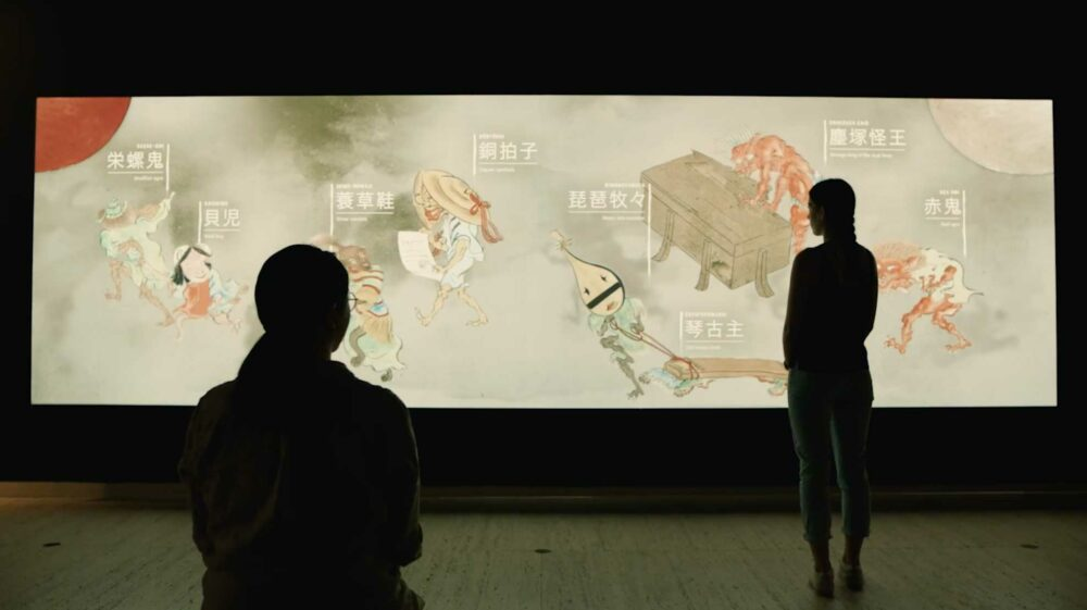 Two women stand in front of interactive touch wall for Japan Supernatural.