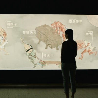 Woman stands in front of Japan Supernatural interactive touch wall.
