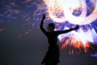 Woman dances in front of data visualisation screen for S1T2 Adobe Remix.