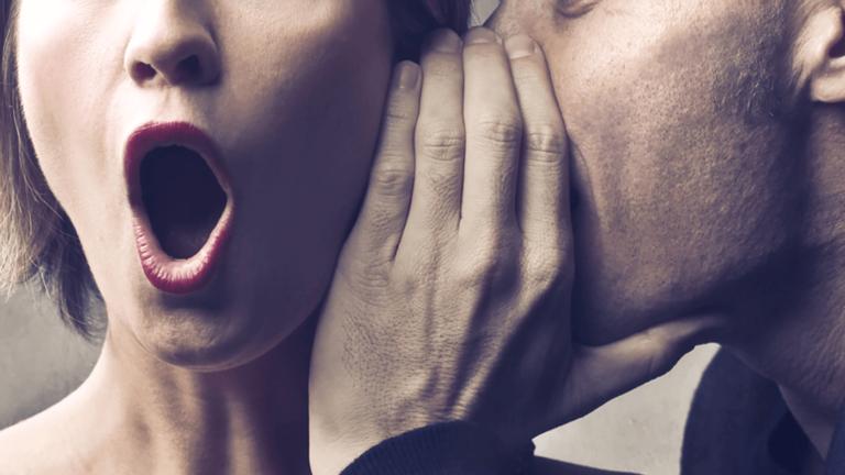 Man whispering in shocked womans ear.
