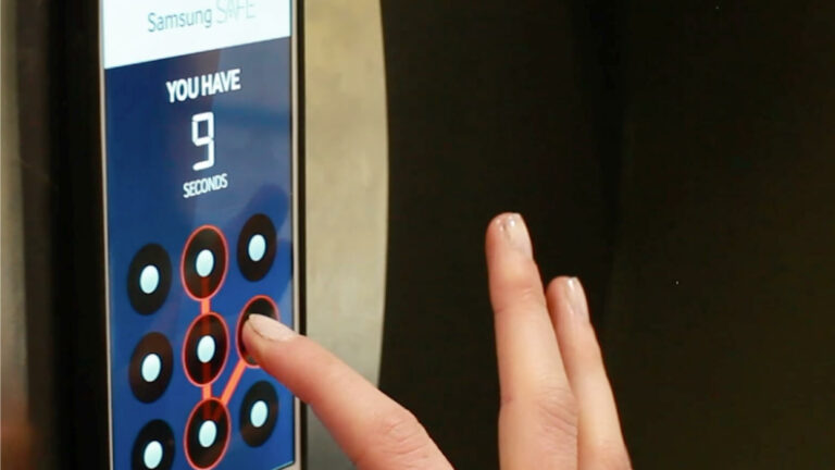 Woman's hand puts a combination into the Samsung Safe smartphone interface.